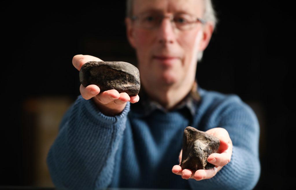 Mike Simms präsentiert zwei versteinerte Dinosaurier-Knochen, gefunden in den 1980ern in Irland.