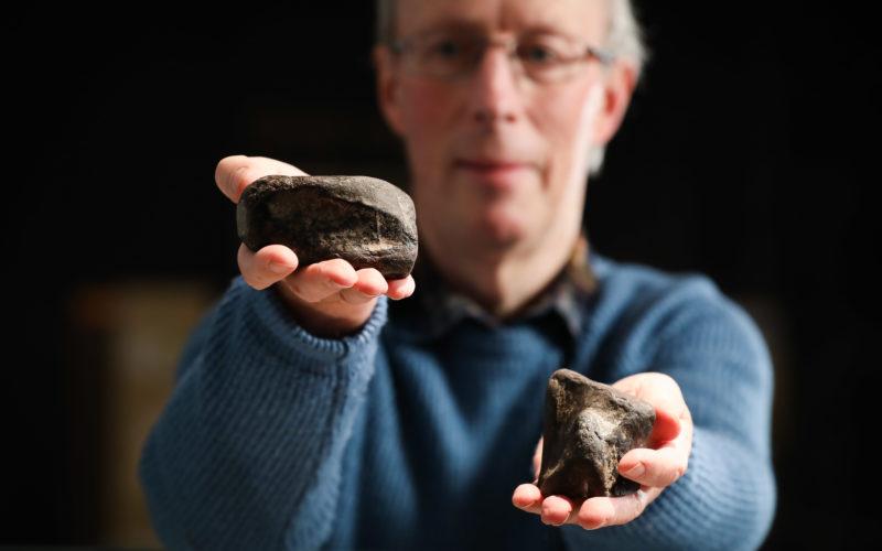 Mike Simms präsentiert zwei versteinerte Knochen von Dinosauriern gefunden in Irland.