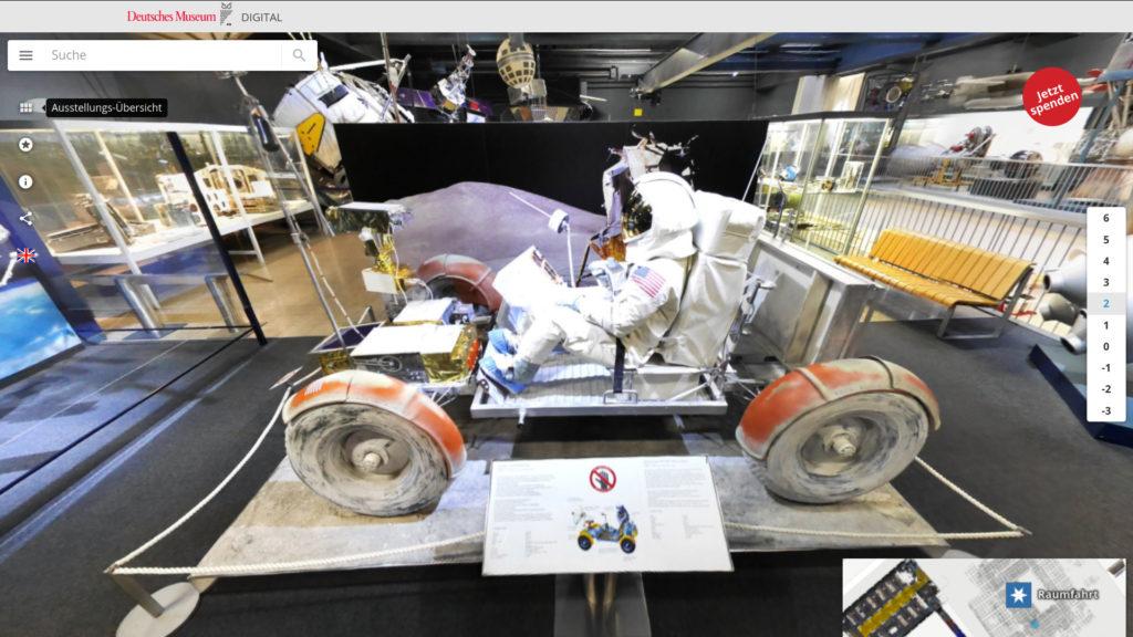 Ein Fahrgestell mit Astronauten im weißen Anzug. Schwarze, staubige Ballonreifen sind mit orangefarbenen Schutzblechen umhüllt. Kein Dach. Zu sehen auf dem Virtuellen Rundgang des Deutschen Museums München.