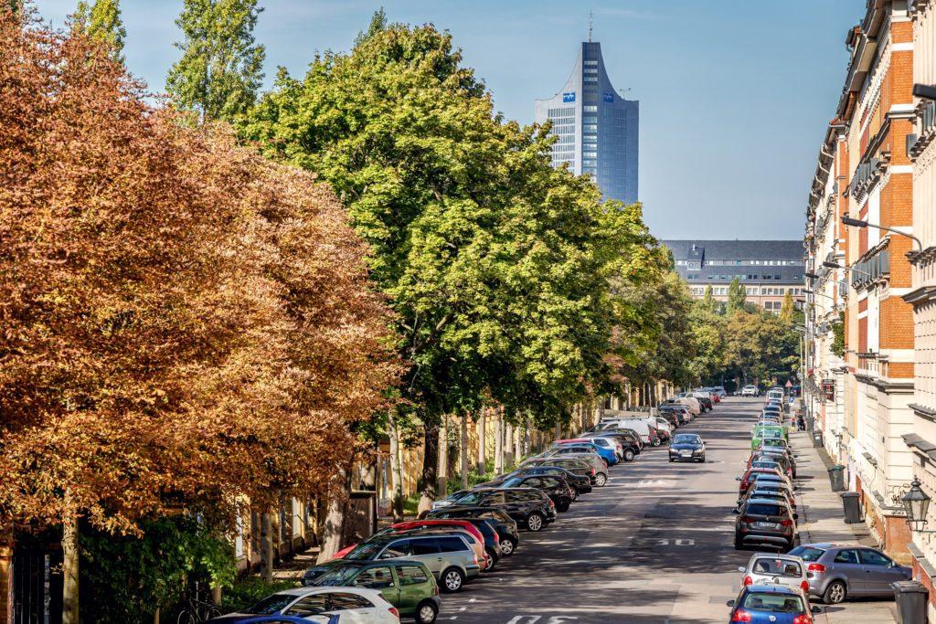 Blick entlang einer Straße. Die Hälfte des Bildes ist eingenommen von Straßenbäumen am linken Straßenrand. Fluchtpunkt in rechter Bildhälfte auf mittlerer Höhe. Häuserzeile am rechten Straßenrand. Straße voll geparkt mit Autos.