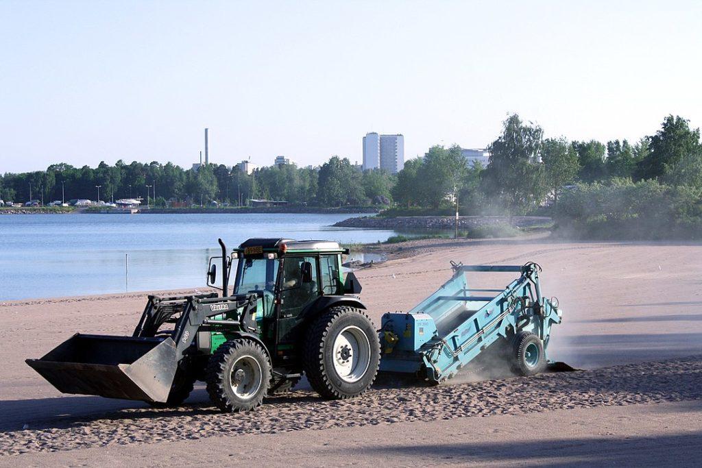 Ein Traktor zieht einen Sandreiniger über einen Sandstrand. Links eine Bucht. Im Hintergrund Bäume. Dahinter ragen zwei Hochhäuser und ein Schornstein in den Himmel.