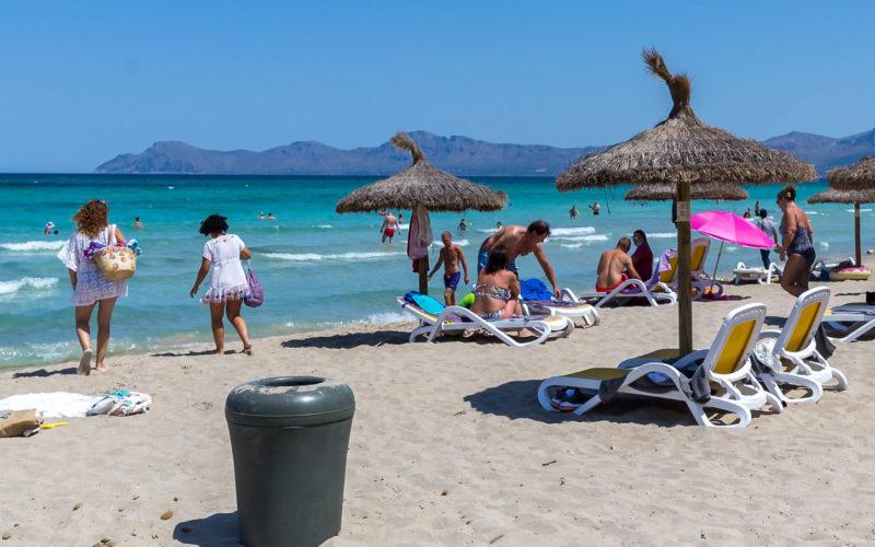 Grauer Mülleimer aus Plastik am Sandstrand. Strohsonnenschirme, Liegen, Personen. Im Hintergrund das Meer un am Horizont Berge.
